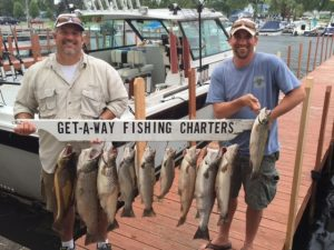 2 men holding fish from Getaway Fishing Charters